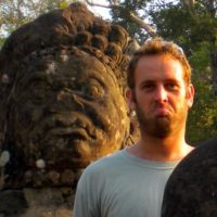 Brian posing with a statue of Angkor Wat, Cambodia