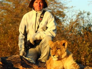 Michael and 8 mo. old female lion, Antelope Park, Zimbabwe