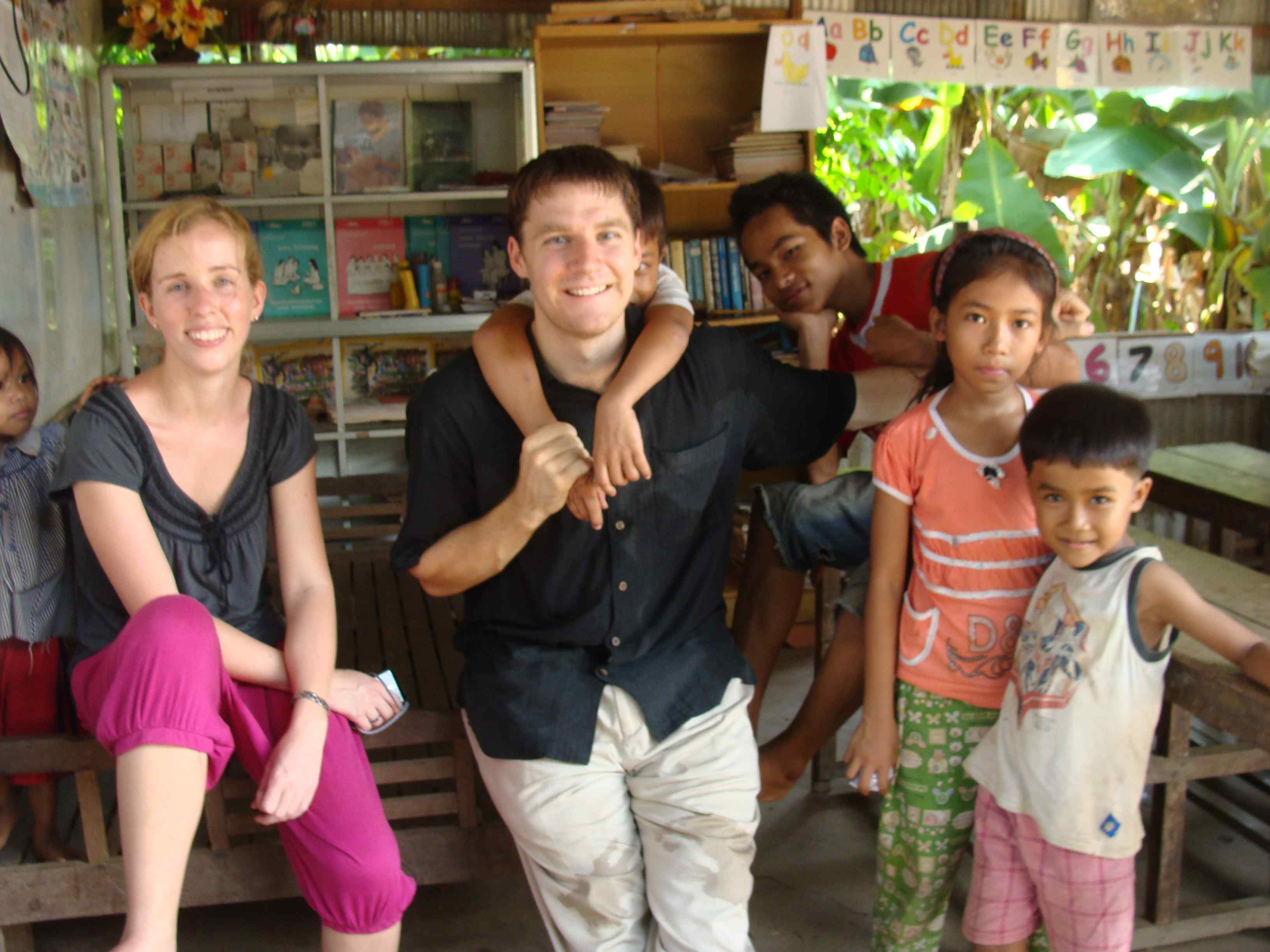 Emily and Steventeacher with kids in Cambodia.