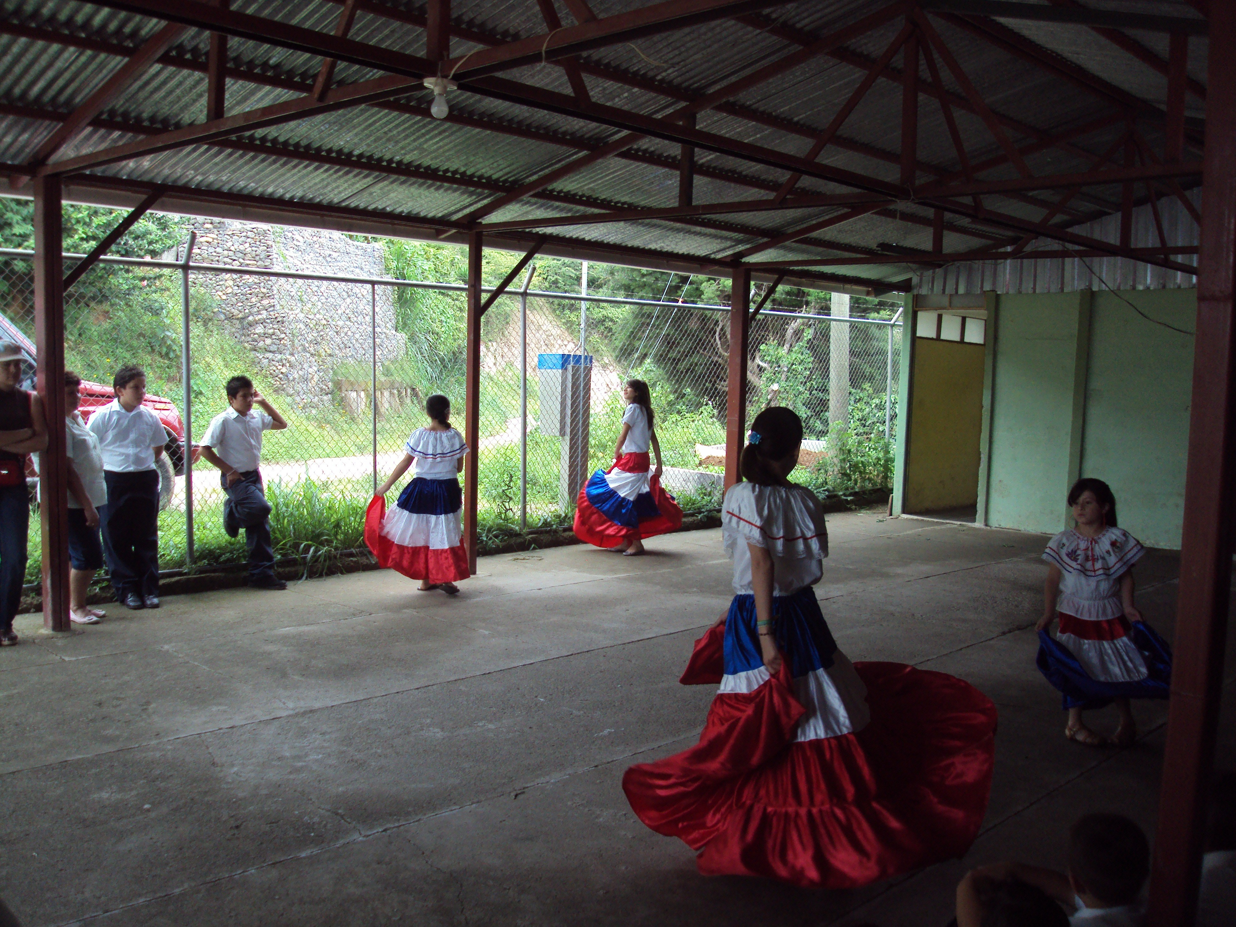 """Students doing """"baile tipico"""" or traditional folk dance."""