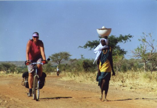 "Nancy Explains: ""Me cycling in Mali. We had the brilliant idea of taking off across a dirt road the map showed cutting through the desert. As we progressed farther, the road condition deteriorated and eventually the road turned into nothing more than a small trail. People assured us that Djenne was ""that way"" so we kept going - for about 80 miles along the little trail going through the desert. We were thrilled when we finally emerged from the desert!"""
