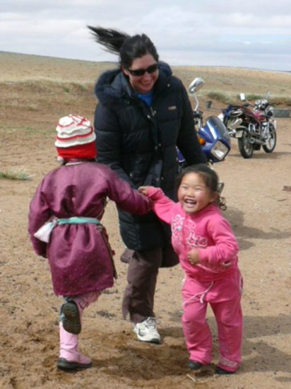Lisa playing with happy kids in Mongolia.