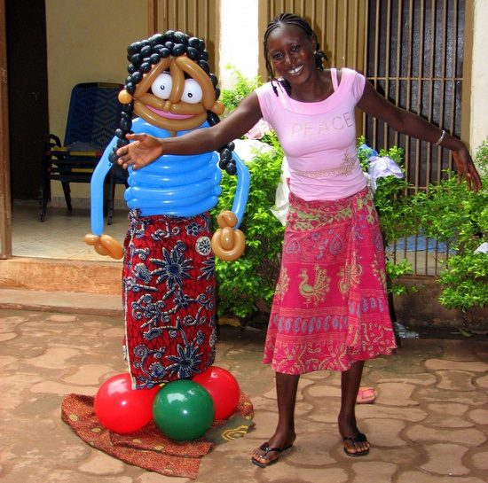 Sara's host family in Mali showing the size of Sara's balloon art!