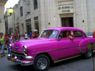 Sarah in an old-fashioned car during Cuba travel!
