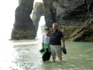 Kelly and her husband at Playa de las Catedrales in the Rias Altas of Galicia, Spain. These rock formations are hidden underwater at high tide. This beach, named a national monument, was named Europe's most beautiful beach.