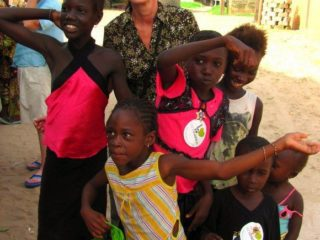 During a visit to the mayor's compound in Sokone, Senegal, children greeted Arlis's group with enthusiasm. Later, they would dance, eat, and enjoy lots of conversation with their hosts.