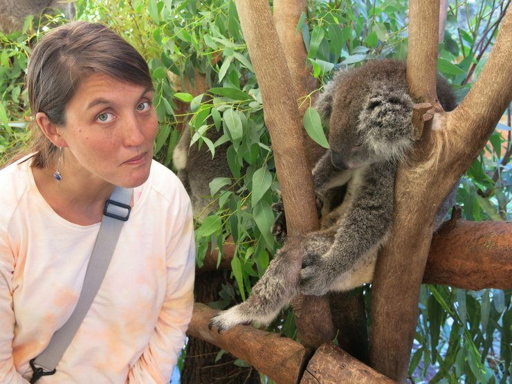 Tasha with a koala in Australia with the look of someone who is disappointed the koalas aren't awake.
