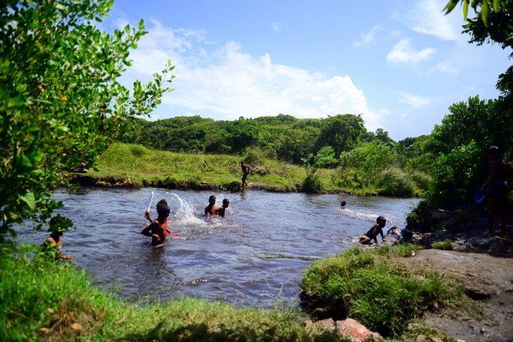 Children Swimming in a Waterhole in the Dominican Republic.