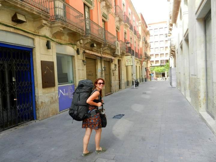 Kelly, walking through a Spanish street with her dusty backpack.