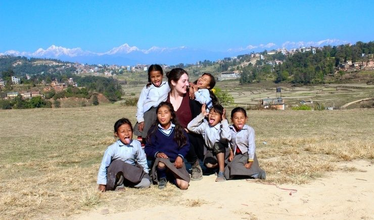Beth and a group of students in front of the Himalayas.