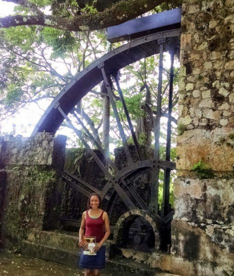 Montego Bay, Jamaica, in front of a preserved water wheel on a former sugar cane plantation. Fenesha is holding  the Toastmasters magazine for the Traveling Toastmaster feature.