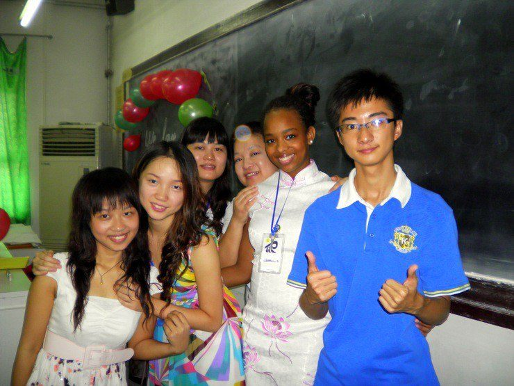 """This picture was taken in Beijing, China with a few of Jamilah's students. She had purchased a traditional Chinese dress, which her students loved! In the back are balloons students arranged alongside the note """"I love you!"""""""