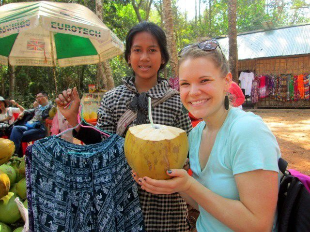 Casey drinking a coconut in Cambodia.