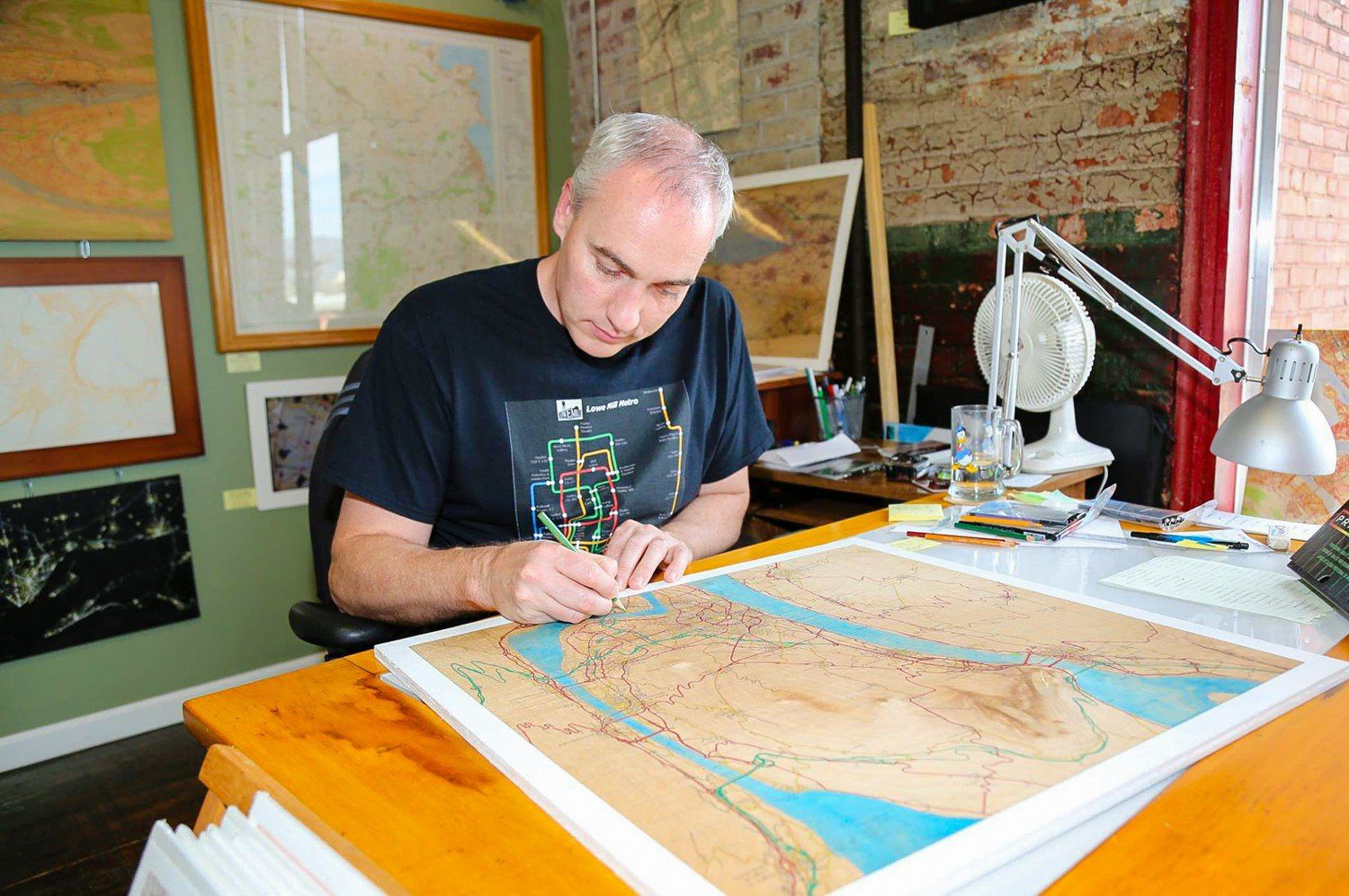 David in his studio, working on one of his maps.