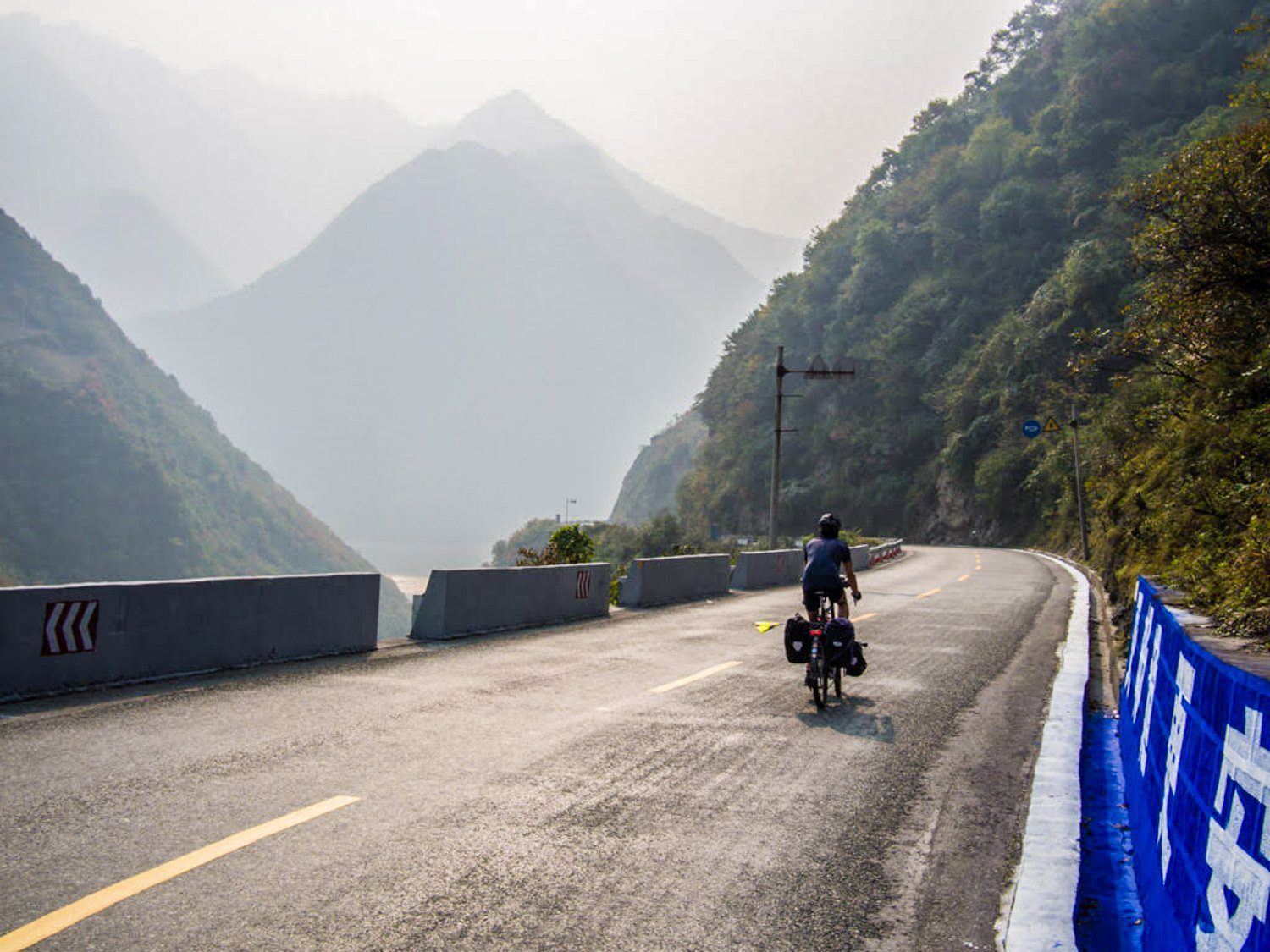 Stephen ascending a misty mountain pass by bike in China.