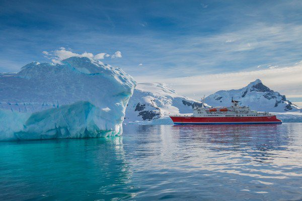 The G Adventures Antarctica Expedition ship near icebergs.