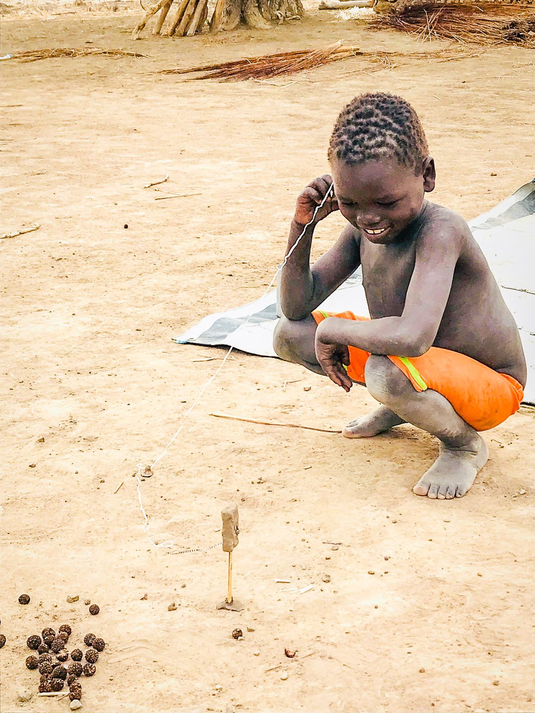 A boy in South Sudan making his own toy.