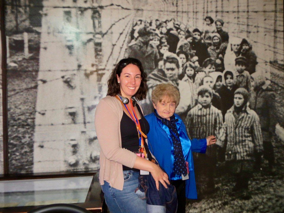 With Eva Kor in front of a liberation photo. The child she is pointing to is herself! The little girl next to her was her twin sister, Miriam.