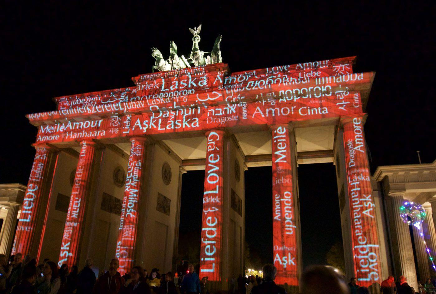 Brandenburg Gate lit up with words. Berlin, Germany: Teacher Fellowships for Social Studies Travel